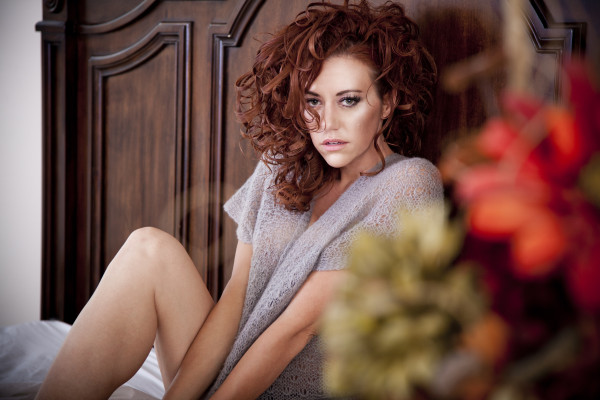 Boudoir photograph of pretty woman with big beautiful red curls in he hair and a grey knit top
