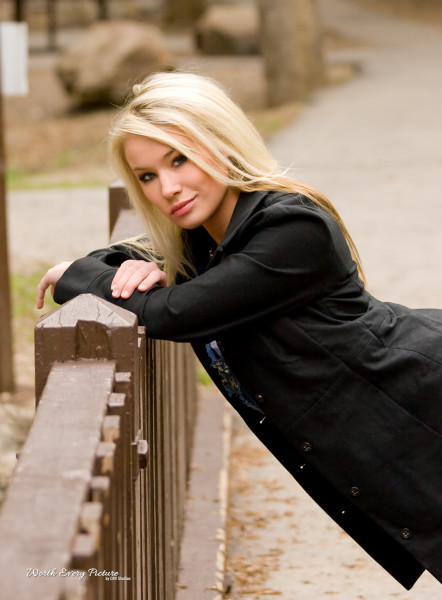 Gorgeous glamour close up shot of young blonde woman wearing a black jacket and leaning on a bridge