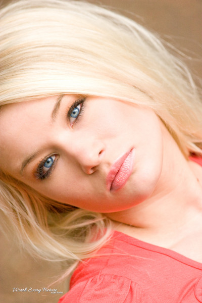 Gorgeous glamour close up shot of young blonde woman wearing a bright orange top with the most stunning blue eyes